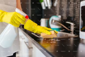 Woman cleaning kitchen cabinets with sponge and spray cleaner. MORE FROM THIS SERIES IN MY PORTFOLIO
